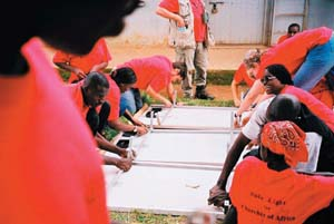 Team members assemble solar panels in Uganda. Photo by: Solar Light for Africa